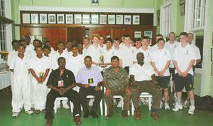 Players of the Guyana U-15 cricket team (rear left) and the members of the visiting English schoolboys side (rear right) gather in the GCC Pavilion in the midst of the CEO of the West Indies Cricket Board, Dr Donald Peters, Minister of Culture, Youth and