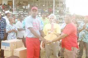 Berbice skipper Esaun Crandon receives the Butcher/Murray trophy from Basil Butcher while Deryck Murray (centre) looks in appreciation.