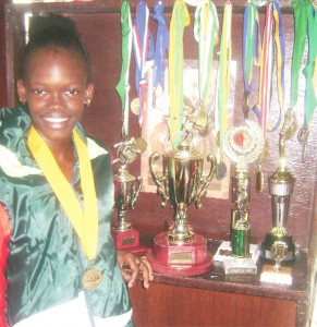 Jevina Straker posing with a few of her trophies and medals at home yesterday. (Rawle Toney photo)