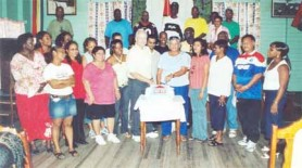 David and Doreen de Caires surrounded by staff members cut the cake on Stabroek News's twentieth anniversary, November 2006.