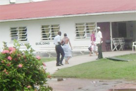 The tortured teen (second, left) with a sheet wrapped around his waist being escorted into the West Demerara Regional Hospital by a policeman yesterday. At right is the hospital security guard. The teen's mother Shirley Thomas (second, right) walks ahead into the hospital. (Photo by Zoisa Fraser)