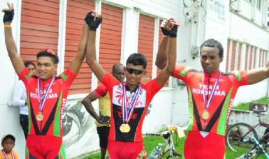 National cyclist, Raynauth Jeffrey (centre) raises the hands of fellow national riders, Alanzo Greaves (left) and Warren '40' McKay after collecting their medals for finishing in the top three of the National Road Race Championships. (Orlando Charles photo)