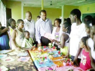 Minister of Culture, Youth and Sport, Dr. Frank Anthony (centre) interacts with children at a summer camp on the East Coast Demerara. (GINA photo)