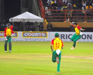TEAM OVER COUNTRY! Krishmar Santokie celebrates the dismissal of countryman Andre Russell.