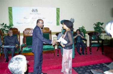 Haitian writer Myriam Chancy shakes then President Bharrat Jagdeo's hand after receiving the Guyana Prize for Literature Caribbean Award in the Fiction category for her book 'The Loneliness of Angels.' Guyana Prize for Literature Management Committee yesterday announced that there will be no regional prize conferred at the upcoming awards ceremony owing to a lack of funding. (Stabroek News file photo)