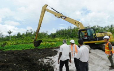 Minister of Works Robeson Benn (left) looking on at the excavation works ongoing at the CJIA on Thursday in the presence of officials from CHEC.