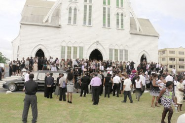 Some of the hundreds of people who turned out to pay their last respects to Bank of Guyana Governor Lawrence Williams, standing outside the St George's Cathedral after his funeral service yesterday. (See Page 15) (Photo by Arian Browne)