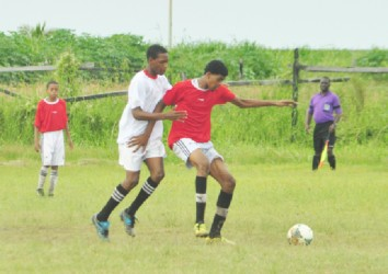 North Georgetown Secondary's Nehemiah Gomes struggling to keep possession of the ball while being marked by a Guyana Industrial Training Centre player during their matchup.