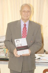 Yesu Persaud with the first volume of his autobiography at the book launch earlier this year (Stabroek News file photo)