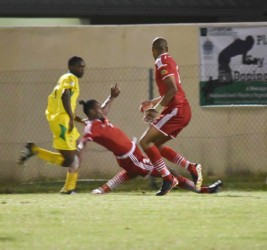 Shaquille Agard (left) on the attack while being challenged by his St. Kitts and Nevis marker during Guyana's final match in the CFU Caribbean Cup Qualification tourney.