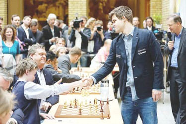 Norwegian world chess champion Magnus Carlsen lent a helping hand to launch his country's Chess in Schools programme recently. He conducted a simultaneous chess exhibition for students and their parents to give stimulus to the activity. In the photo Carlsen accepts a girl's resignation.