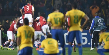 Stunned Brazilian players watch on as Paraguay celebrate their penalty shootout win.