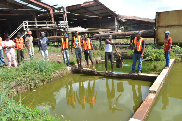 Workers stand at the rancid pond from which they are forced to dip water and which they reported has made them sick. (Social Protection Ministry photo)