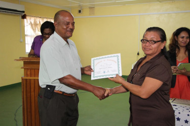 Regional Executive Officer, Carl Parker, presents a certificate to Theresa Mansingh at the closing ceremony of the 'Self-Reliance and Success in Business' workshop, held at the Indigenous Peoples Conference Hall in Lethem. (Ministry of the Presidency photo)