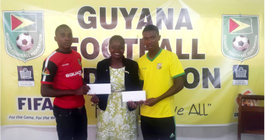 Alpha United's Delon Lanferman (left) and Pele's Jumane Somerset collecting their plane ticket from GFF Vice President Attorney-at-Law Thandi McAllister at the federation's office prior to their departure for the MLS Combine in Curacao