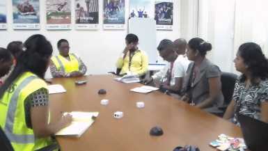 Minister within the Social Protection Ministry, Simona Broomes (third, left) and her team talking to some of the Qualfon staff, at Qualfon Goedverwating