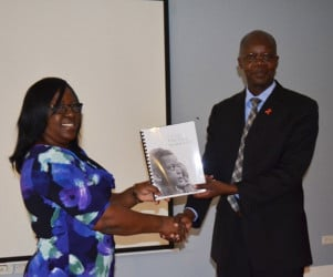 Minister in the Ministry of Public Health Dr Karen Cummings receiving a copy of the strategy from Dr Martin Odiit, UNAIDS Country Coordinator(GINA photo)