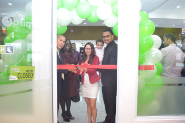 Cutting the ribbon for the opening of Optique Vision Care in Giftland Mall. (From left are Minister of Public Health, Dr. George Norton, Minister within the Ministry of Public Health, Dr. Karen Cummings and Madonna Narine, Co-founder of Optique (centre) ,Manager, Dhani Narine and their daughter, Madison Narine.