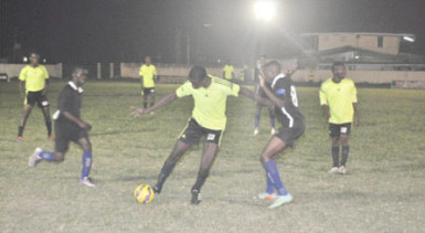 Clive Matthews of Grove Hi-Tech (centre) trying to maintain possession of the ball while being challenged by a Pouderoyen player during their team's matchup at the Farm ground in the Stag Beer Super XVI Knockout Championships.