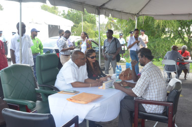 Minister of State Joseph Harmon (left) listening to one of the citizens.