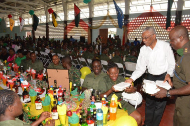President David Granger (second from right) serving lunch at Base Camp Ayanganna yesterday. (Ministry of the Presidency photo)