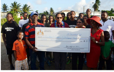 Prime Minister Moses Nagamootoo (centre) and wife Sita Nagamootoo (next to him) hands over the cheque to Founder of the Group Beryl Haynes in the presence of community members. (GINA photo)