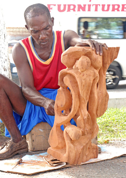 Sculptor Marvin Phillips working on a piece of art on Main Street back in September 2014. (Stabroek News file photo)