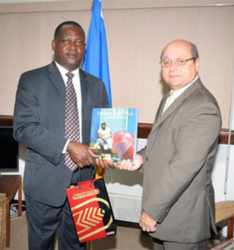 Barbados Minister of Industry Donville Innis exchanging gifts with Cuban envoy Francisco Fernandez Pena in Bridgetown recently.