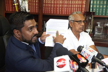 Attorney Gerald Ramdeen displays a document during a press conference at his law chambers on Cornelio Street, Woodbrook on Wednesday. At right is Baliram Ramdial, president of the combine four Cane Farmers Associations.