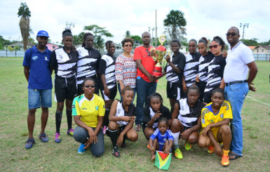 GFF President Wayne Forde in the presence of Minister within the Ministry of Indigenous Peoples Valerie Garrido-Lowe hands over the championship trophy to the victorious Fruta Conquerors-A side following the conclusion of the NAWF women's Championships yesterday. (Orlando Charles photo)
