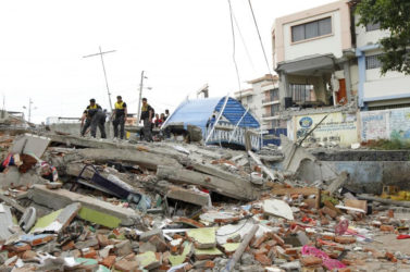 Police officers stand on debris after an earthquake struck off Ecuador's Pacific coast, at Tarqui neighbourhood in Manta April 17, 2016. REUTERS/Guillermo Granja