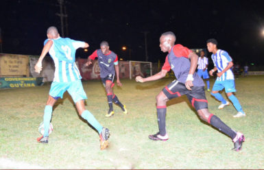 Jamal Gibbs (12) in the process of initiating a left side cross while being pursued by Joshua Brown (right) and Dwight Peters (left) of Alpha United during their GFF Stag Beer Elite League matchup