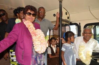 President David Granger gets a feel of the driver's seat while Minister of Social Cohesion Amna Ally (first, left), Region Four Chair Genevieve Allen (background) and Peter Lewis (centre) look on.(Ministry of the Presidency photo)