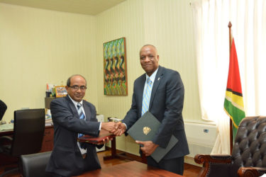 Indian High Commissioner to Guyana, Venkatachalam Mahalingam (left) and Minister of State, Joseph Harmon shake hands after the signing (Ministry of the Presidency photo)