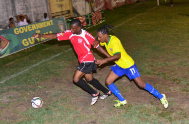 Gregory Richardson (yellow) of Pele battling to win the ball from a Buxton United player during their team's matchup in the GFF Stag Beer Elite League at the GFC ground. (Orlando Charles photo)