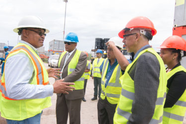 An official of Tiger Tanks (left) speaks about the company's work in Guyana during a tour of Muneshwers new port facility at Houston yesterday.