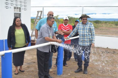 Minister of Indigenous Peoples' Affairs Sydney Allicock turns on the main at the well at Culvert City, in Region Nine in the presence of the Guyana Water Incorporated's Chief Executive Officer Richard Van West- Charles and other officials on Wednesday. (Government Information Agency photo)