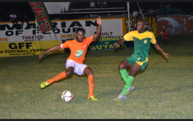 Reshawn Sandiford (left) of Fruta Conquerors trying to evade the impending challenge from Alden Lawrence of the GDF during the matchup at the Tucville Community ground in the GFF Stag Beer Elite League