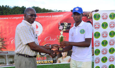 All-rounder Ronaldo AliMohammed collects his MVP trophy from referee Grantley Culbard