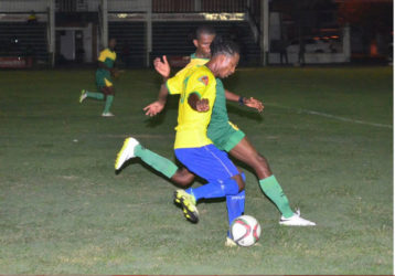 Gregory Richardson of Pele trying to shake off the pursuit of his GDF marker during their matchup in the GFF Stag Beer Elite League at the Camp Ayanganna ground Sunday. (Orlando Charles photo)