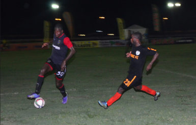 Trayon Bobb (right) of Slingerz FC chasing down Alpha United centre-half Solomon Austin for possession of the ball during their GFF Stag Beer Elite League  matchup at the Camp Ayanganna ground