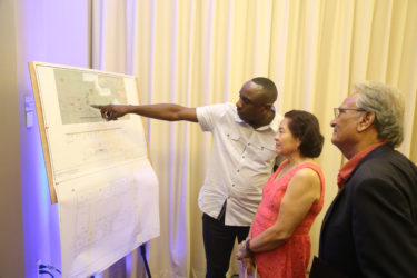 In this Keno George photo, the designer of Step by Step's dream building, Kenrick Thomas (left) outlines his plan to First Lady Sandra Granger and Minister of Education Dr Rupert Roopnaraine.