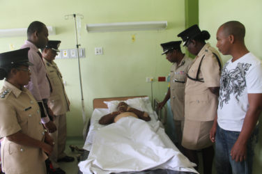 Assistant Commissioner David Ramnarine and other senior officers of the Guyana Police Force visit wounded Lance Corporal Andrew Richardson at Georgetown Public Hospital. (Guyana Police Force photo)
