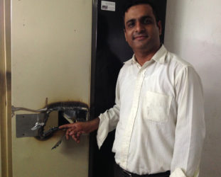 Chief Executive Officer of the Alesie Group of Companies Jai Keswani pointing to a lock on a metal cabinet that the bandits torched