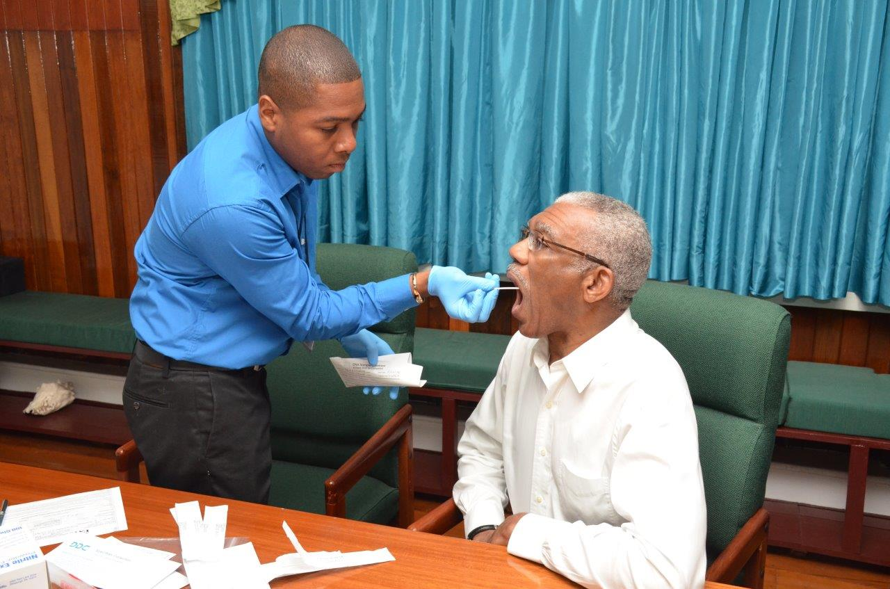 Shawn Manbodh taking the DNA sample from President David Granger (Ministry of the Presidency photo)