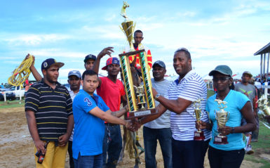 Release The Beast and its handlers collect the winner's trophy from Banks DIH's Mortimer Stewart yesterday at the Bush Lot Turf Club. (Orlando Charles photo)