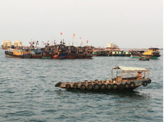 Fishing boats with Chinese national flags are seen at a harbour in Baimajing, Hainan province, April 7, 2016. REUTERS/Megha Rajagopalan
