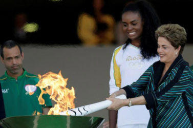 Brazil's President Dilma Rousseff (R) lights a cauldron with the Olympic Flame next to Fabiana Claudino, captain of the Brazilian volleyball team, during the Olympic Flame torch relay at Planalto Palace in Brasilia, Brazil, yesterday. REUTERS/UESLEI MARCELINO