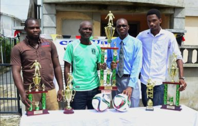 Members of the C & A Unique Incorporated/South Quakers Ministry inaugural Golden Jubilee Futsal Knockout Championship launch party from left to right Tourney Coordinator Carlos Griffith, Lawrence December, Alistair Griffith and Ryan Patterson posing with the respective tourney trophies.