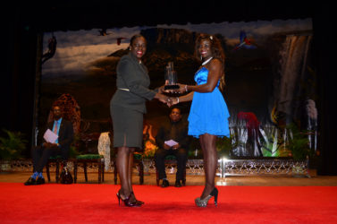 Wednesday night capped off a banner season for Alisha Fortune after she was crowned the 2015 Sportswoman-of-the-Year. Above she receives her award from Minister Nicolette Henry. (Orlando Charles photo)